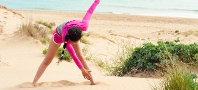 Woman in pink top doing yoga on the beach