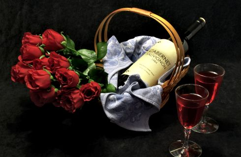 Red roses in a basket with a bottle of wne
