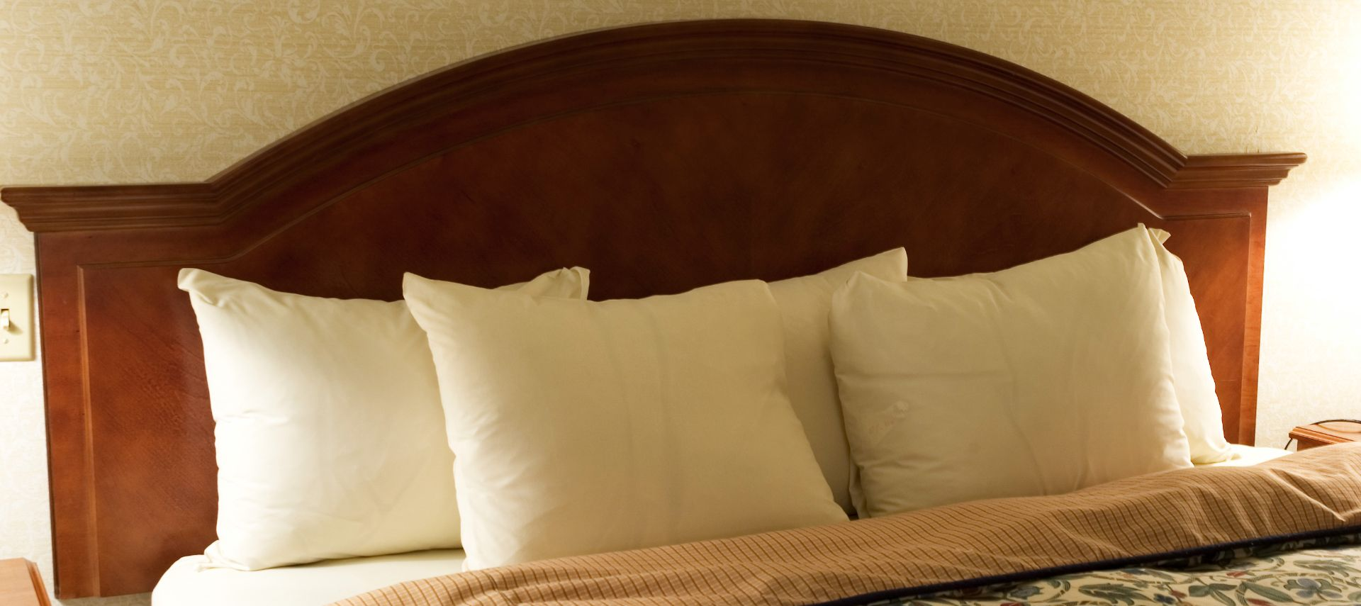 Wooden headboard with several fluffy white pillows