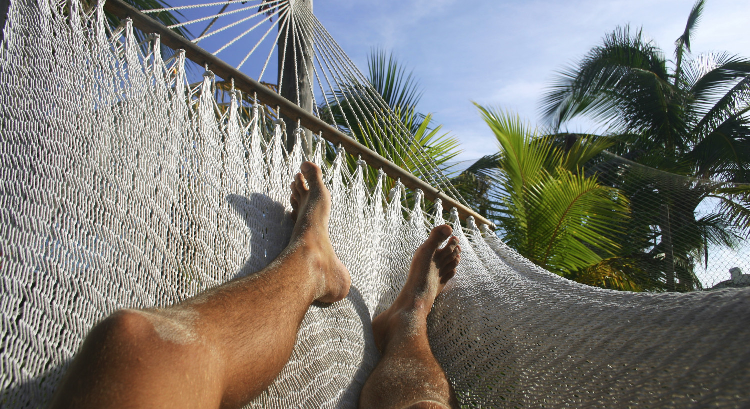 A man's tanned legs relax on a rope hammock under palm trees.